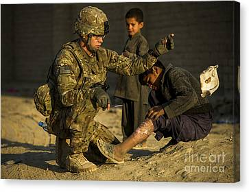 Airman Provides Medical Aid To A Local Canvas Print by Stocktrek Images