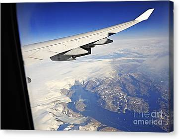 Airplane Wing Over Snowy And Rocky Coastline Canvas Print by Sami Sarkis