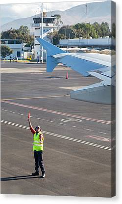 Airport Worker Guides Jet Airliner Canvas Print