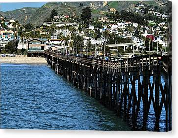 Along The Pier Canvas Print by Michael Gordon