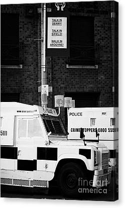 Armoured Psni Land Rovers Under Protest Sign Banner On Crumlin Road At Ardoyne  Canvas Print