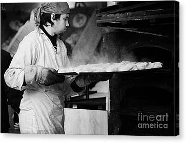 Baker Removing Tray Of Bread With Steam Rising From An Outdoor Wooden Baking Oven On A Stall At The Christmas Market Berlin Germany Canvas Print by Joe Fox