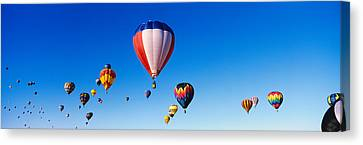 Balloons Floating In Blue Sky Canvas Print by Panoramic Images