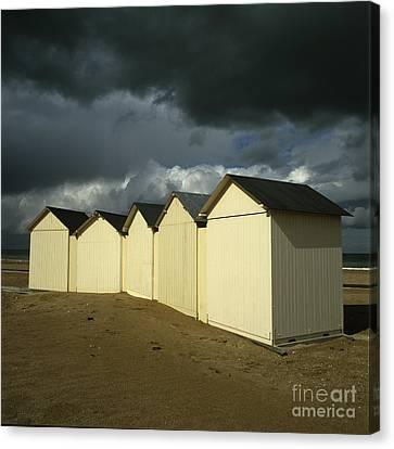 Beach Huts Under A Stormy Sky In Normandy. France. Europe Canvas Print by Bernard Jaubert