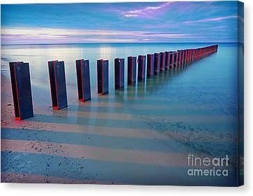 Beach Pylons At Sunset Canvas Print by Martin Konopacki