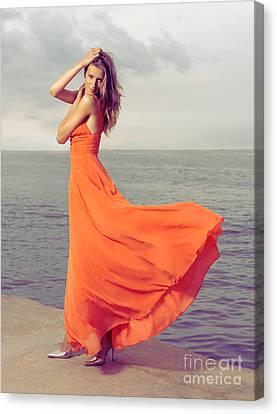 Beautiful Woman In Orange Dress On Sea Shore Canvas Print by Oleksiy Maksymenko
