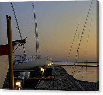 Boats Moored To Pier At Sunset Canvas Print by Charles Beeler