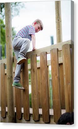 Boy Climbing Over Wooden Fence Canvas Print