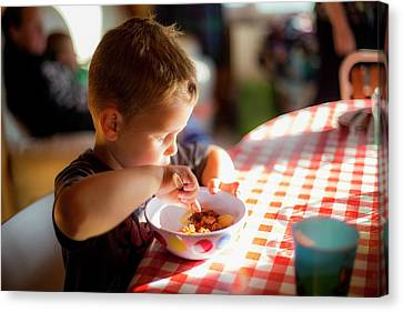 Boy Sitting At Table Eating A Meal Canvas Print by Samuel Ashfield