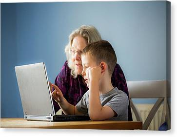 Boy Using Laptop With Grandmother Canvas Print by Samuel Ashfield