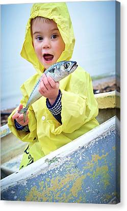 Boy Wearing Raincoat Holding A Mackerel Canvas Print by Ruth Jenkinson