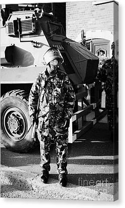 British Army Soldier In Riot Gear With Saxon Armoured Personnel Carrier Vehicle On Crumlin Road At A Canvas Print