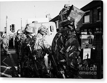 British Army Soldiers In Riot Gear Stand Guard On Crumlin Road At Ardoyne Shops Belfast 12th July Canvas Print by Joe Fox