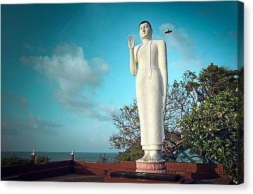 Buddha Statue And Crow Canvas Print by Paul Kennedy