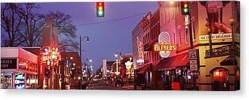 Buildings Along The Street Lit Canvas Print by Panoramic Images
