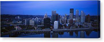 Buildings In A City At Dusk Canvas Print by Panoramic Images