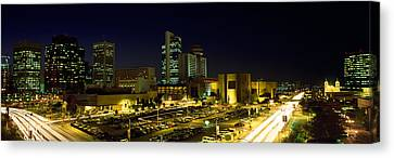 Built Canvas Print - Buildings In A City Lit Up At Night by Panoramic Images