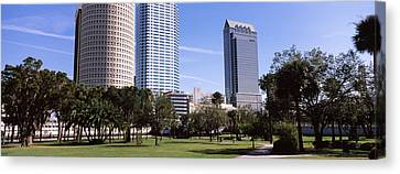 Buildings In A City Viewed From A Park Canvas Print by Panoramic Images