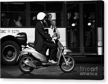 Business Man In Suit And White Helmet On Scooter Commutes Past Bus Full Of Passengers Through Piazza Canvas Print by Joe Fox