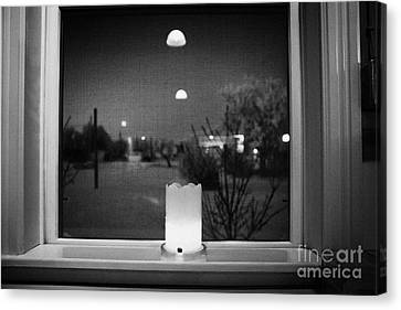 candle in the window looking out over snow covered scene in small rural village of Forget Saskatchew Canvas Print by Joe Fox