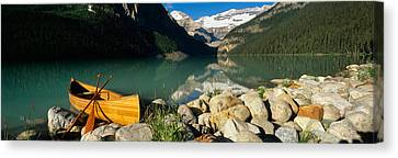 Canoe At The Lakeside, Lake Louise Canvas Print by Panoramic Images