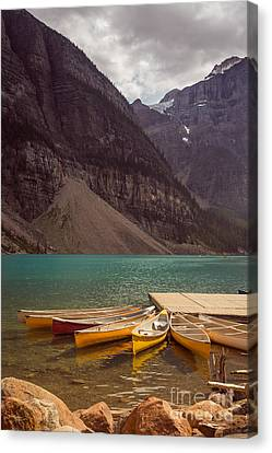 Canoe For Rent In Banff's Moraine Lake Canvas Print by Edward Fielding