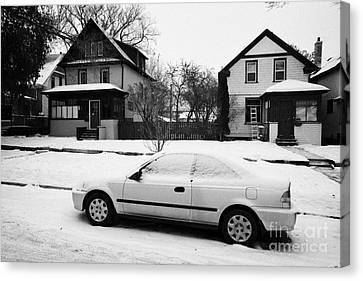 car covered in snow parked by the side of the street in front of residential homes caswell hill Sask Canvas Print by Joe Fox
