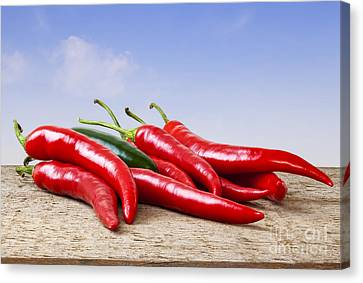 Chilli Peppers On Rustic Background Canvas Print by Colin and Linda McKie