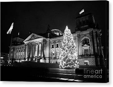christmas tree and german flag flying fluttering on flagpole outside reichstag building Berlin Germany Canvas Print by Joe Fox