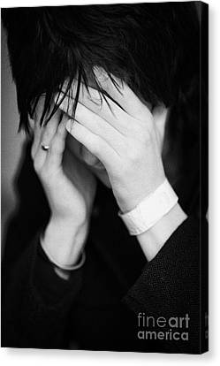 Close Up Of Young Dark Haired Teenage Man Sitting With His Head In His Hands Hiding His Face Staring Canvas Print by Joe Fox