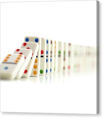 Colourful Dominoes Falling Down Canvas Print by Science Photo Library