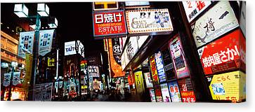 Commercial Signboards Lit Up At Night Canvas Print by Panoramic Images