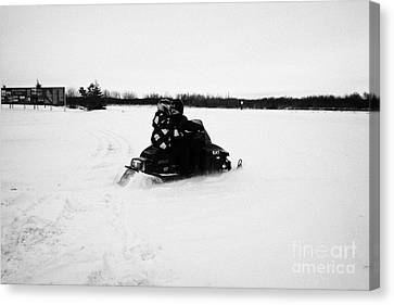couple on a snowmobile going cross country Kamsack Saskatchewan Canada Canvas Print