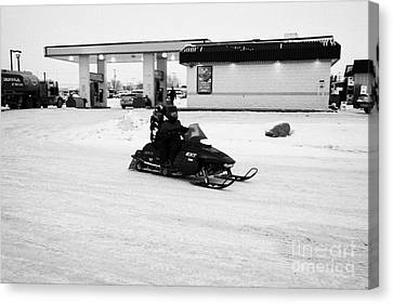 couple on a snowmobile leaving a gas station Kamsack Saskatchewan Canada Canvas Print