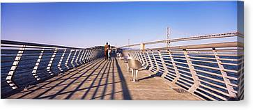 Couple Walking On A Pier, Bay Bridge Canvas Print by Panoramic Images