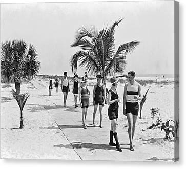 Couples Strolling Along The Pathway On The Beach. Canvas Print by -