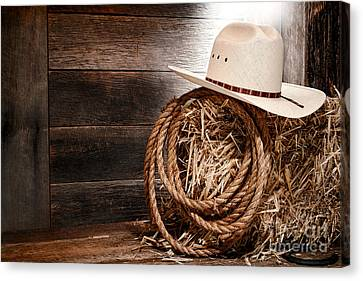 Cowboy Hat On Hay Bale Canvas Print by Olivier Le Queinec