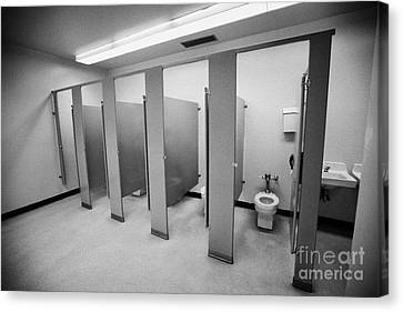 cubicle toilet stalls in womens bathroom in a High school canada north america Canvas Print by Joe Fox