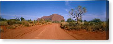 Desert Road And Ayers Rock, Australia Canvas Print by Panoramic Images