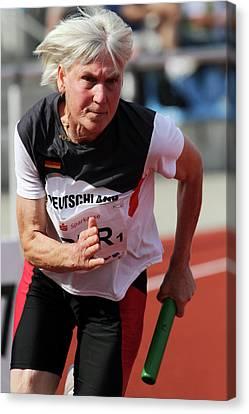 Determined Female Senior Athlete Running Canvas Print by Alex Rotas