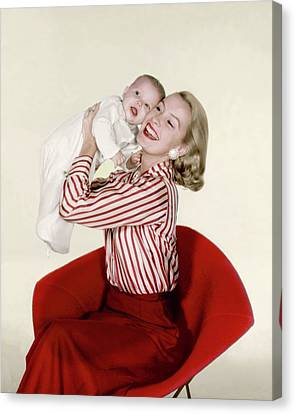 Dina Merrill Holding A Baby Canvas Print by John Rawlings