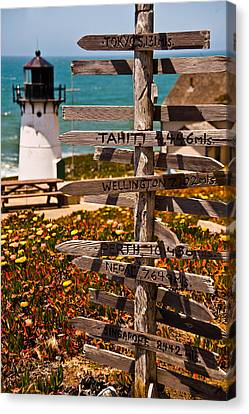 Directional Signs On A Pole With Light Canvas Print by Panoramic Images