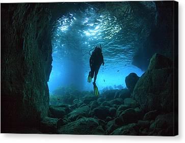 Diver Swimming Through A Sea Cave Canvas Print
