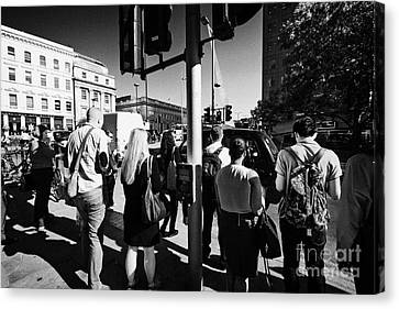 early morning commuters waiting to cross the road pedestrian crossing London England UK Canvas Print by Joe Fox