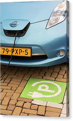 Electric Car At A Charging Station Canvas Print by Ashley Cooper