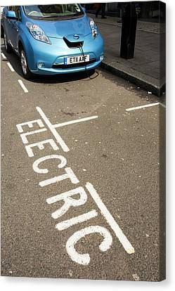 Electric Car At A Recharging Station Canvas Print by Ashley Cooper