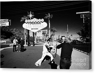 elvis impersonator taking photos with tourists at the welcome to fabulous Las Vegas sign Nevada USA Canvas Print by Joe Fox