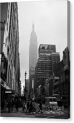 Empire State Building Shrouded In Mist As Pedestrians Crossing Crosswalk On 7th Ave And 34th Street  Canvas Print by Joe Fox