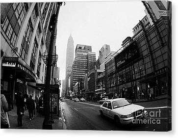 Empire State Building Shrouded In Mist As Yellow Cab Taxi New York City Canvas Print by Joe Fox
