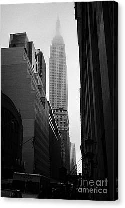 empire state building shrouded in mist in amongst dark cold buildings on 33rd Street new york city Canvas Print